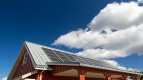 Den Tid schackningsperioden av rörande vitmoln och blå himmel över tak med solpaneler installerade uhd 4k lager videofilmer