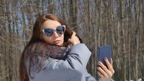 Den tidiga vårståenden av den unga kvinnan som tar selfie i, parkerar utomhus på trädbakgrund under solig varm dag stock video