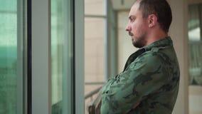 Den tidigare militära mannen står vid fönstret, det regnar stock video