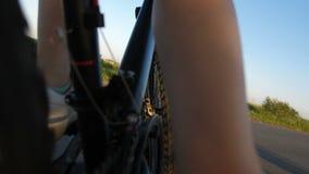 Den tillbaka closupsikten av flicka` s lägger benen på ryggen på cykelhjul arkivfilmer