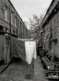 Den tillbaka gränden av traditionella brittiska terrasserade hus med tvagningen på linjer och växter i krukor som in tas, hebden  arkivfoto