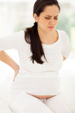 Den tillbaka gravida kvinnan smärtar Royaltyfri Bild