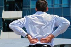 den tillbaka mannen smärtar Affärsman som rymmer hans lägre baksida Smärta lättnadsbegreppet Arkivbild