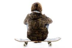 den tillbaka pojken poserar den sittande skateboarden Royaltyfria Foton
