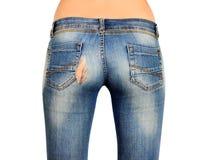 Den tillbaka sidan av den kvinnliga röven i isolerad sönderriven jeans Arkivbild