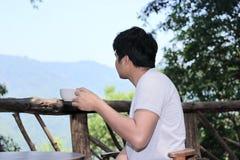 Den tillbaka sikten av barn kopplade av den asiatiska mannen som dricker kaffe och ser den härliga naturen Arkivbild