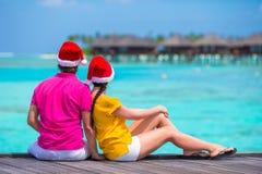 Den tillbaka sikten av barn kopplar ihop, i att koppla av för jultomtenhattar Arkivfoto