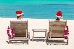 Den tillbaka sikten av barn kopplar ihop, i att koppla av för jultomtenhattar Arkivbilder