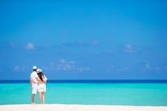 Den tillbaka sikten av barn kopplar ihop på den vita stranden på sommar arkivfoto