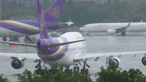 Den tillbaka sikten av boeing 747 av thailändska flygbolag åker taxi på vått flygfält på regnigt väder arkivfilmer