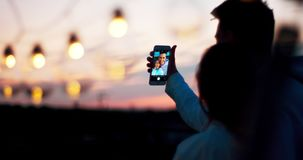 Den tillbaka sikten av de lyckliga le paren av två vänner som tar selfies under solnedgången på taket, dekorerade med rad arkivfilmer