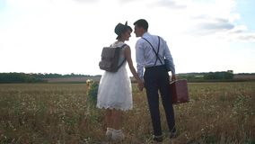 Den tillbaka sikten av de lyckliga nygifta personerna som rymmer händer i det soliga fältet Den tappning klädde bruden rymmer buk lager videofilmer