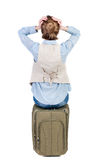Den tillbaka sikten av den chockade kvinnan i väst sitter på en resväska Arkivfoton
