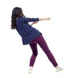 Den tillbaka sikten av den stående flickan som drar ett rep från överkant eller, klamra sig fast intill s Royaltyfri Foto