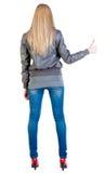 Den tillbaka sikten av den stående unga blonda kvinnavisningen tummar upp Fotografering för Bildbyråer