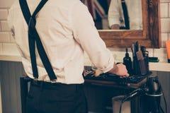 Den tillbaka sikten av en barberare shoppar stylisten som organiserar hans hjälpmedel och equi arkivfoton
