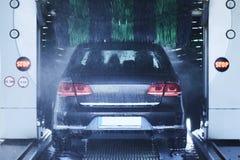 Den tillbaka sikten av en carwash som gör ren en bil med att rotera, borstar royaltyfri fotografi