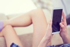 Den tillbaka sikten av en kvinna räcker genom att använda den smarta telefonen med slut för tom skärm upp Vit telefon med en svar Arkivfoton