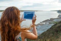 Den tillbaka sikten av en luffare för ung kvinna gör fotoet med den bärbara minnestavlakameran under henne semestrar i byängar arkivfoton