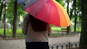Den tillbaka sikten av en oigenkännlig kvinnaspring med det färgrika paraplyet under regnet i staden parkerar Slowmotion skott lager videofilmer
