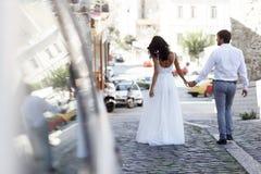 Den tillbaka sikten av ett romantiskt par av nygifta personer går på den gamla gatan Grekland Br?llop i Grekland royaltyfria bilder