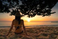 Den tillbaka sikten av gravida kvinnan sitter på sand och hållande ögonen på solnedgång på den tropiska stranden Koppla av för ha arkivbild