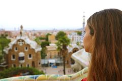 Den tillbaka sikten av kvinnan parkerar in Guell som beundrar landskap från terrassen av parkera, Barcelona, Spanien Arkivfoton