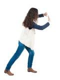 Den tillbaka sikten av kvinnan skjuter väggen Royaltyfria Foton