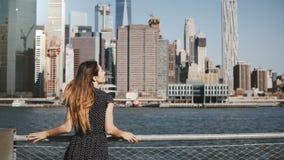 Den tillbaka sikten av den lyckliga kvinnliga handelsresanden med hår som blåser i vinden som tycker om New York horisont som lyf lager videofilmer