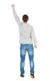 Den tillbaka sikten av mannen i rutig skjorta lyftte hans näve upp i victo Fotografering för Bildbyråer