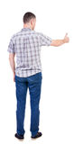 Den tillbaka sikten av mannen i rutig skjorta visar upp tummar Arkivbild