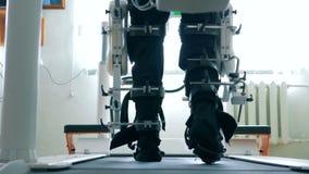 Den tillbaka sikten av mannen lägger benen på ryggen att få rörd av en gå simuleringsmaskin Virtuell verklighetsimulator för tålm stock video