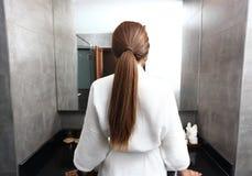 Den tillbaka sikten av den nätta unga kvinnan slogg in hår royaltyfria foton