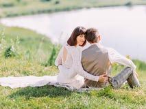 Den tillbaka sikten av nygifta personerna som sitter på gräset och tycker om naturen Arkivbild