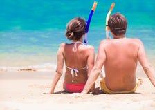 Den tillbaka sikten av par med snorkelkugghjulsammanträde på sand sätter på land Royaltyfria Bilder