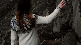 Den tillbaka sikten av den unga brunettkvinnan i lopapeysa som går till och med, vaggar och att fotvandra i bergen bara i blåsig  stock video