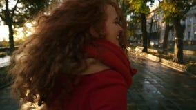 Den tillbaka sikten av den unga caucasian kvinnan som kör joyfully i en färgrik höst, parkerar av gränden som tycker om höstlövve lager videofilmer