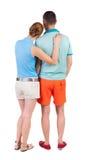 Den tillbaka sikten av unga omfamna par i kortslutningar kramar och ser Royaltyfri Foto