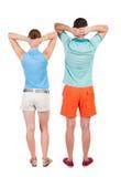 Den tillbaka sikten av unga omfamna par i kortslutningar kramar och ser Royaltyfri Fotografi
