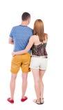 Den tillbaka sikten av unga omfamna par i kortslutningar kramar och ser Royaltyfria Bilder