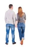 Den tillbaka sikten av unga omfamna par (mannen och kvinnan) kramar och ser Royaltyfria Bilder