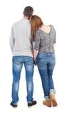 Den tillbaka sikten av unga omfamna par (mannen och kvinnan) kramar och ser Royaltyfri Bild