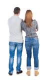 Den tillbaka sikten av unga omfamna par (mannen och kvinnan) kramar och ser Fotografering för Bildbyråer