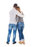 Den tillbaka sikten av unga omfamna par (mannen och kvinnan) kramar och ser Royaltyfri Fotografi