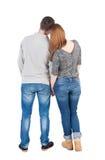Den tillbaka sikten av unga omfamna par (mannen och kvinnan) kramar och ser Arkivfoto