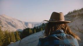 Den tillbaka sikten av den unga turist- flickan som bara sitter på, vaggar hållande ögonen på härlig bergsikt på den Yosemite nat arkivfilmer