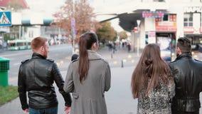 Den tillbaka sikten av vänner går på gatan Stiliga män och två nätta flickor som pratar på gå Steadicam skott, långsam mo lager videofilmer