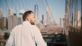 Den tillbaka sikten av den vuxna europeiska mannen kommer upp till panorama för den Brooklyn bron, ser omkring och trycker på hår lager videofilmer