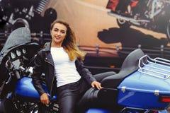 Den tillfälliga härliga kvinnan sitter på en stor turist- motorcykel på det ljusa leendet för gatan på en solig dag Arkivbild