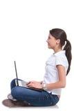 Den tillfälliga kvinnan sitter med bärbara datorn Fotografering för Bildbyråer